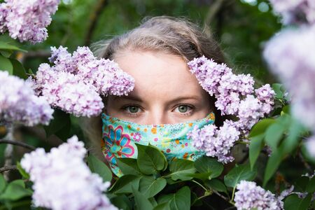 Young blonde woman smells lilac tree blossom through facial mask. Conceptual image of coronavirus quarantine and allergy.