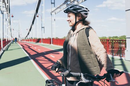Young blonde woman riding a bicycle on a bridge during sunny spring morning in Kyiv, Ukraine.