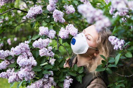 Young blonde woman smells lilac tree blossom through FFP2 respirator. Conceptual image of coronavirus quarantine and allergy.