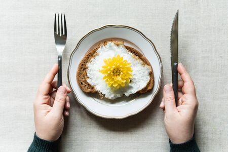 Conceptual image of having breakfast with fried egg toast. Yellow chrysanthemum flower instead of yolk served on a white plate Banque d'images