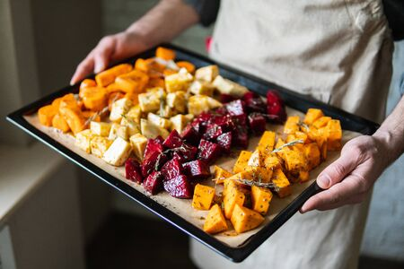 Male hands holding oven tray with vegetables mix. Vegetarian man cooking sweet potatoes and other veggies at home.
