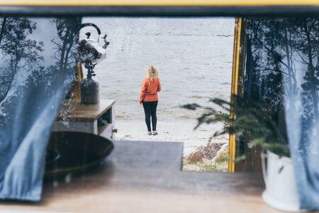 Young blond woman standing next to camper van overlooking the frozen winter sea. View through the open door.