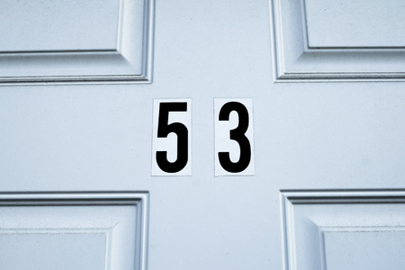 design abstract: the white door number fifty three  with simple pattern Stock Photo