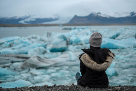 women traveller sit on the ground and looking for iceberg in jokulsarlon glacier lagoon