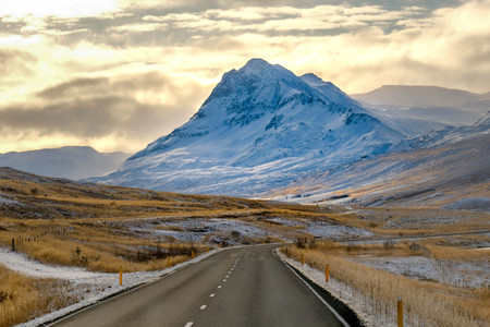 long Road in iceland with Snow mounrtain background, green grass field turn to yellow. Road curve. afternoon time gold cloud Banco de Imagens