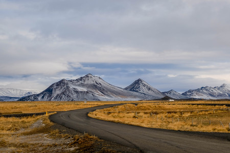 Dirt small route with beautiful snow mountain background grass yellow field in north iceland near detifoss