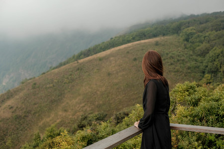 Traveler asia woman look out at viewpoint on the woooden  fence on Mountain   Kew Mae Pan,Doi Inthanon Chiang Mai Northern Thailand