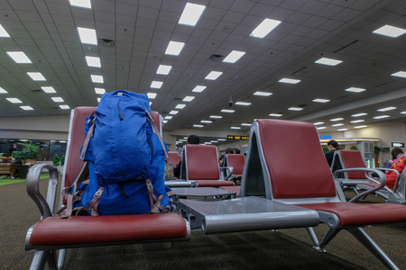 backpack bag leave on the chair in terminal airport waiting for boarding time