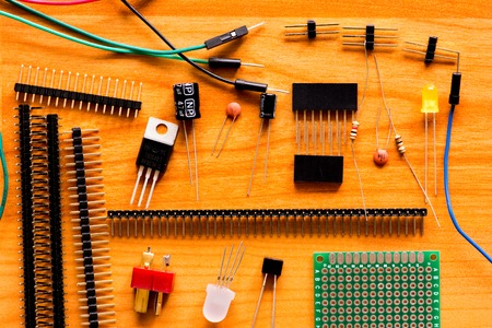 leds: Group of various electronic components: logical digital microchips transistors capacitors resistors LEDs etc. randomly located on wooden floor