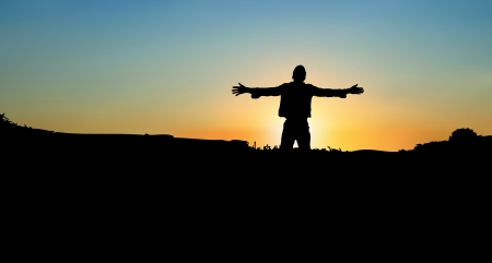 A silhoutte of man worshipping on a mountain at sunset Ilustracja