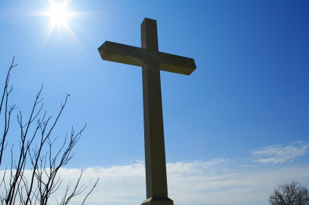 Cross and sun on bright sky photo