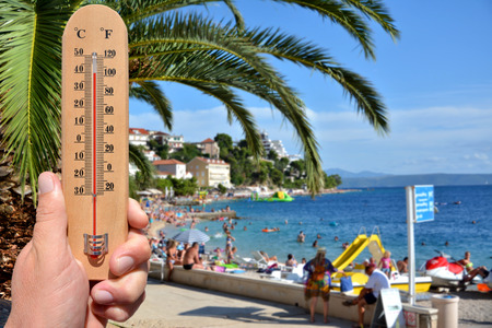 high scale: A thermometer scale shows extreme high temperatures during a heat wave and beach in background. Skin cancer warning