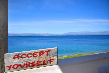 accept yourself on old plank with blurred sea background
