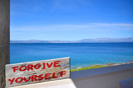 happenings: Forgive yourself on old plank with blurred sea background