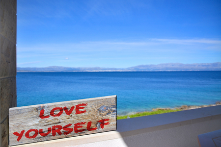 yourself: Love yourself on old plank with blurred sea background