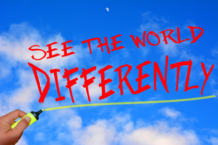 differently: See the world differently text with marker on blurred background