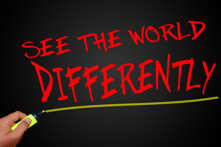 differently: See the world differently text with marker on dark background
