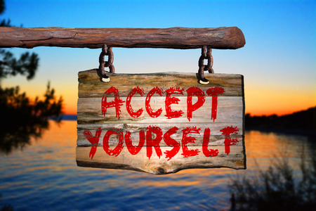happenings: Accept yourself sign on old wood with a blurred sunset on background