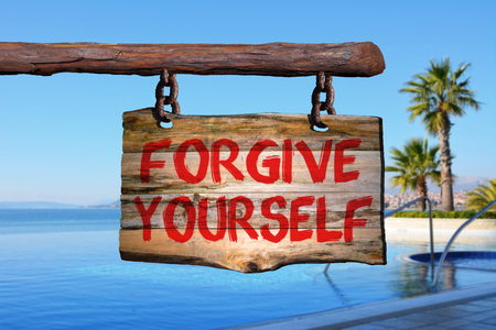 perdonar: Forgive yourself sign on old wood with a blurred sea scape on background