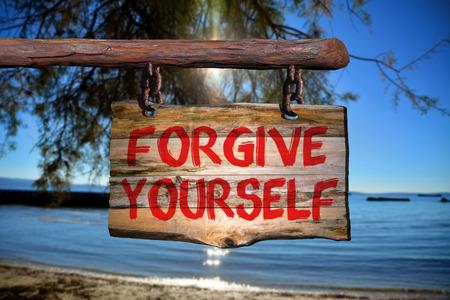 to forgive: Perdona a s� mismo signo en la madera vieja con una playa en el fondo borroso