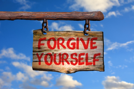 forgive: Forgive yourself sign on old wood with a blurred sky on background Stock Photo