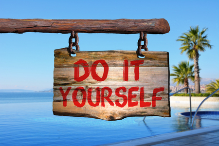 learned: Do it yourself sign on old wood with a blurred pool and sea on background