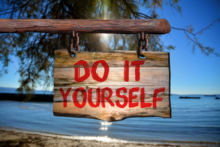 happenings: Do it yourself sign on old wood with a blurred beach on background