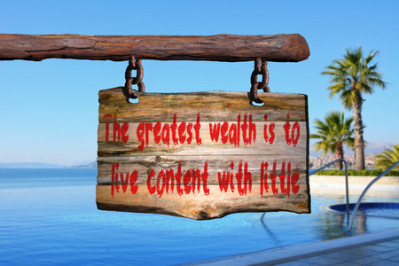 happenings: Wealth quote on old wood with a blurred beach on background