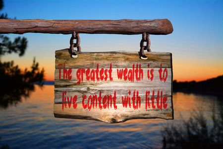 happenings: Wealth quote on old wood with a blurred sunset on background