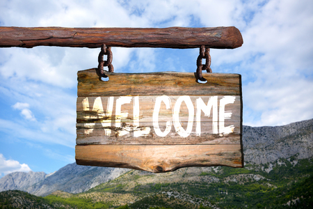 homecoming: Welcome sign on old wood with a blurred mountain on background Stock Photo