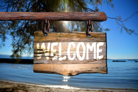 green door: Welcome sign on old wood with a blurred beach on background