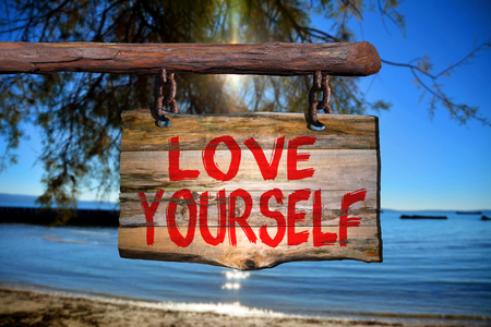 happenings: Love yourself sign with beach blurred background