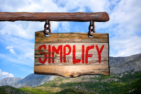 Simplify motivational phrase sign on old wood with blurred background