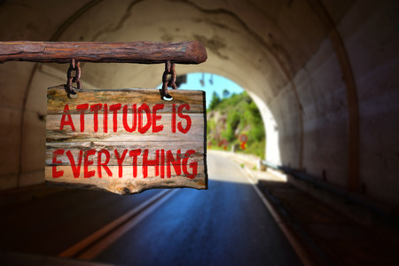 behaving: Attitude is everything motivational phrase sign on old wood with blurred background