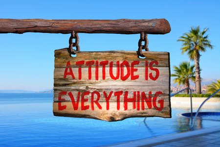 Attitude is everything motivational phrase sign on old wood with blurred background