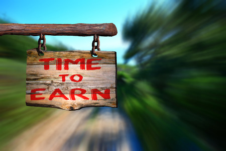 earn: Time to earn sign with blurred background Stock Photo