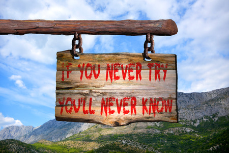 newer: If you newer try... motivational phrase sign on old wood with blurred background