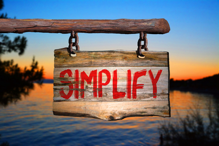 clarify: Simplify motivational phrase sign on old wood with blurred background