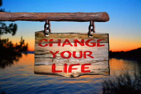 Change your life motivational phrase sign on old wood with blurred background Stockfoto