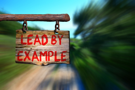 Lead by example motivational phrase sign on old wood with blurred background