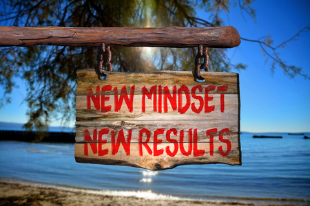New mindset new results motivational phrase sign on old wood with blurred background