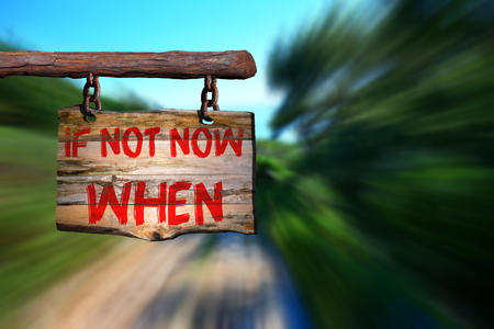 If not now when motivational phrase sign on old wood with blurred background