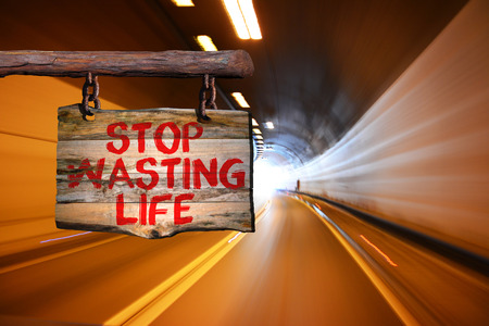 wasting: Stop wasting life motivational phrase sign on old wood with blurred background