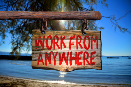 Work from anywhere motivational phrase sign on old wood with blurred background
