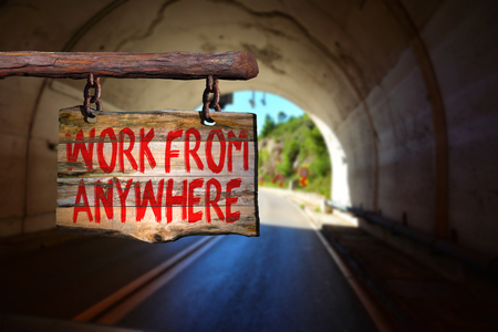 anywhere: Work from anywhere motivational phrase sign on old wood with blurred background