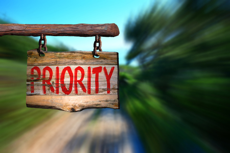 phrase: Priority motivational phrase sign on old wood with blurred background