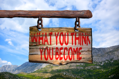 become: What you think you become motivational phrase sign on old wood with blurred background