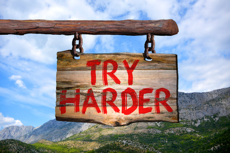 harder: Try harder motivational phrase sign on old wood with blurred background Stock Photo
