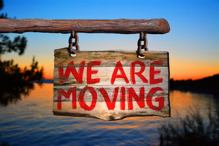 We are moving motivational phrase sign on old wood with blurred background