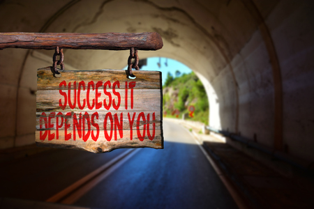 depends: Success it depends on you motivational phrase sign on old wood with blurred background Stock Photo